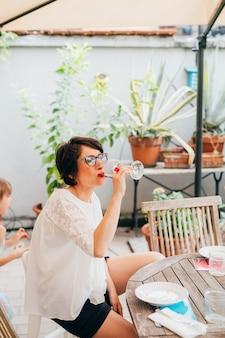 W połowie dorosła kobieta siedzi plenerowego taras ma lampkę wino