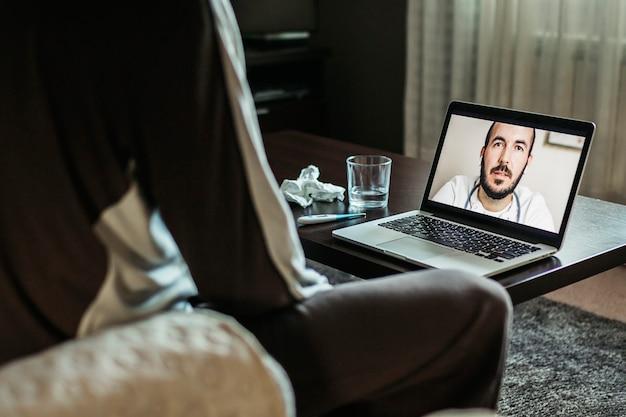 W połowie dorosły mężczyzna omawia medycynę z lekarzem przez połączenie wideo za pośrednictwem laptopa, siedząc w domu
