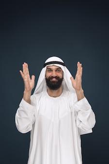 W połowie portret arabski saudyjski biznesmen na ciemnoniebieskiej przestrzeni. młody mężczyzna model stojący i uśmiechnięty