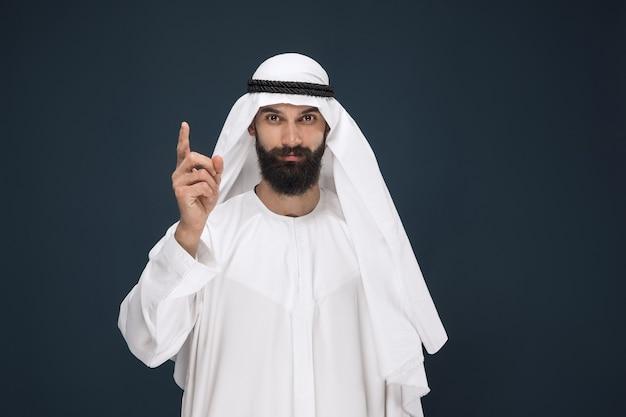 W połowie portret arabski saudyjski biznesmen na ciemnoniebieskiej ścianie. młody mężczyzna model uśmiecha się i wskazuje. pojęcie biznesu, finanse, wyraz twarzy, ludzkie emocje.