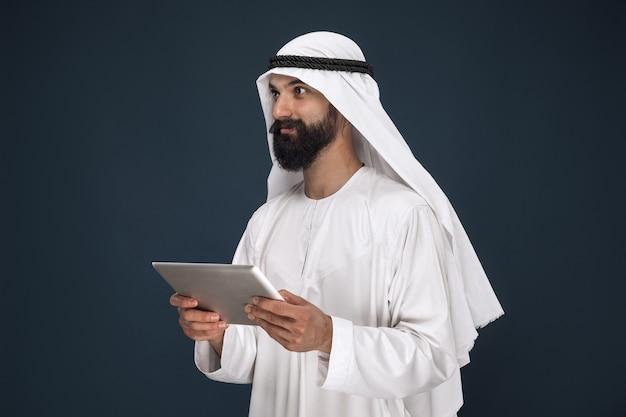 W połowie portret arabski saudyjski biznesmen na ciemnoniebieskiej ścianie. młody model mężczyzna za pomocą tabletu lub gadżetu. pojęcie biznesu, finanse, wyraz twarzy, ludzkie emocje, technologie.