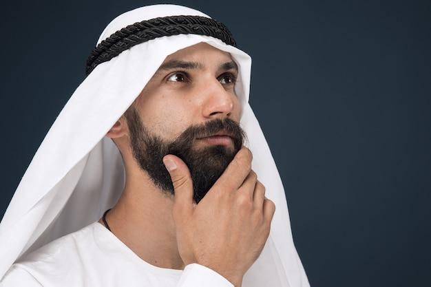W połowie portret arabskiego saudyjskiego biznesmena na ciemnoniebieskiej ścianie studio