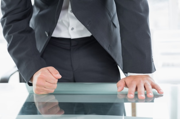 W połowie sekcja biznesmen z zaciskającą pięścią na biurowym biurku