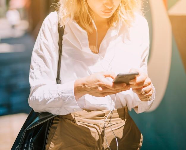 W połowie sekcja blondynki młoda kobieta używa telefon komórkowego przy outdoors