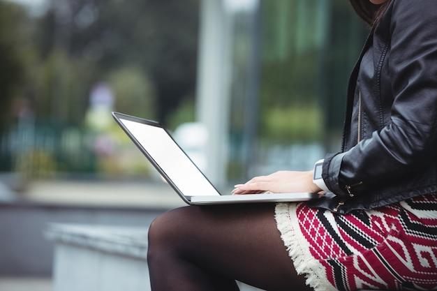 W połowie sekcja kobieta używa laptop