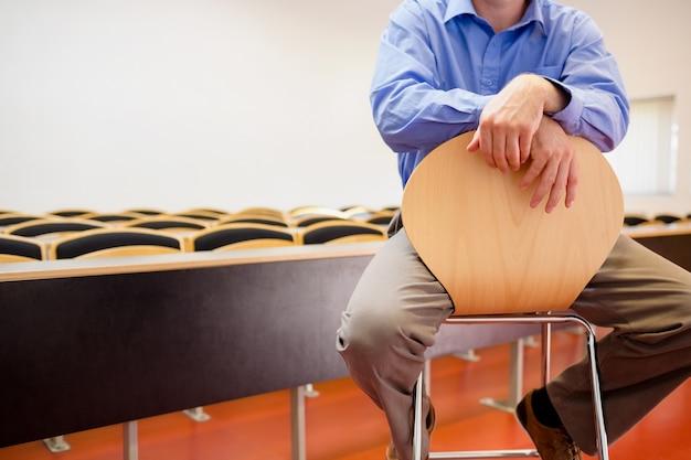 W połowie sekcja męski nauczyciel siedzi na krześle w odczytowej sala