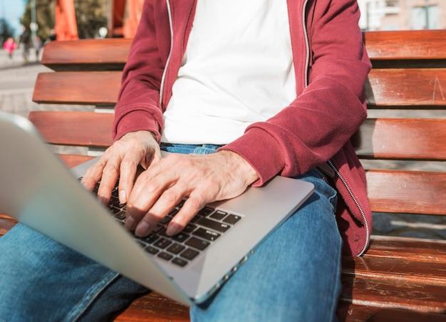 W połowie sekcja mężczyzna obsiadanie na drewnianej ławce pisać na maszynie na laptopie