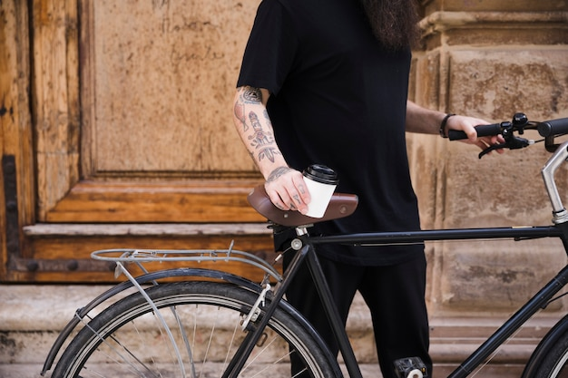 W połowie sekcja mężczyzna pozycja z rowerowego mienia takeaway filiżanką