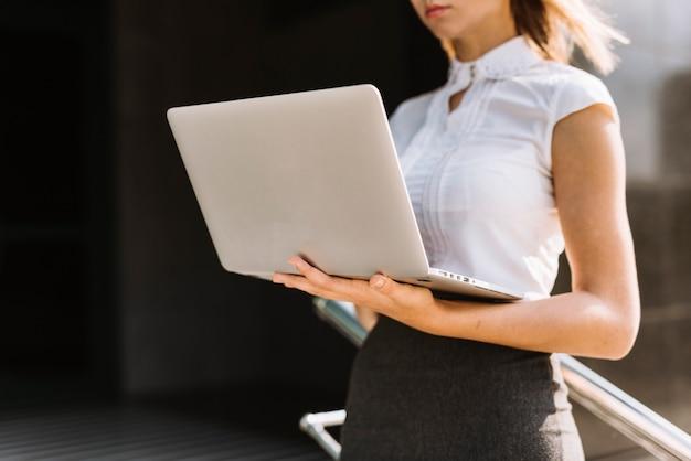 W połowie sekcja młody bizneswomanu mienia laptop przy outdoors