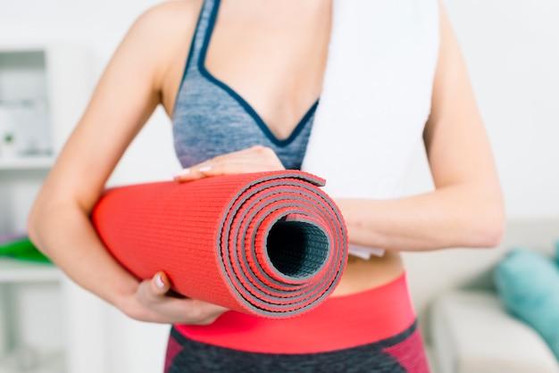 W połowie sekcja sprawności fizycznej młoda kobieta trzyma czerwoną ćwiczenie matę