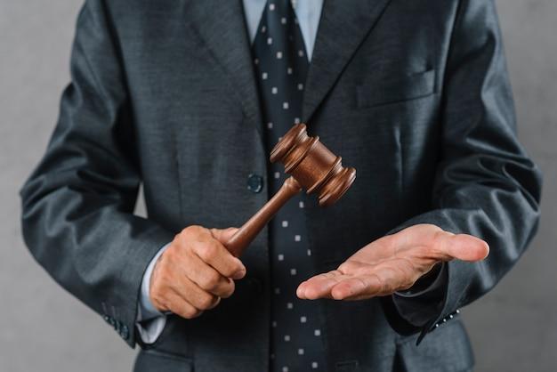 W połowie sekcja trzyma drewnianego dobniaka w ręce męski prawnik