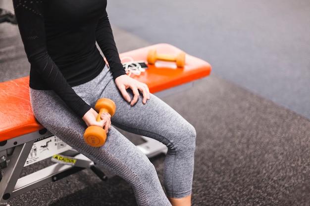 W połowie sekcja widok kobiety ręka ćwiczy z dumbbell w gym