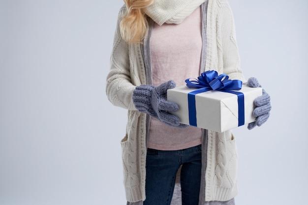W połowie sekcji anonimowa kobieta trzyma prezent na nowy rok