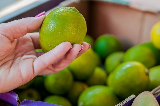 W połowie sekcji kobieta kupuje słodkie wapno w supermarkecie. kobieta kupuje owoce w organicznym zielonym rynku. kobieta, wybierając świeży wapno