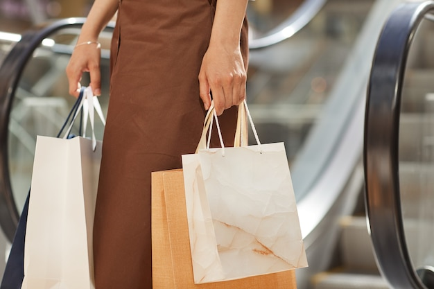 W połowie sekcji portret eleganckiej młodej kobiety trzymającej torby na zakupy stojąc przy schodach ruchomych w centrum handlowym, kopia przestrzeń