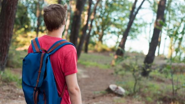 W połowie strzał chłopiec z plecakiem w lesie