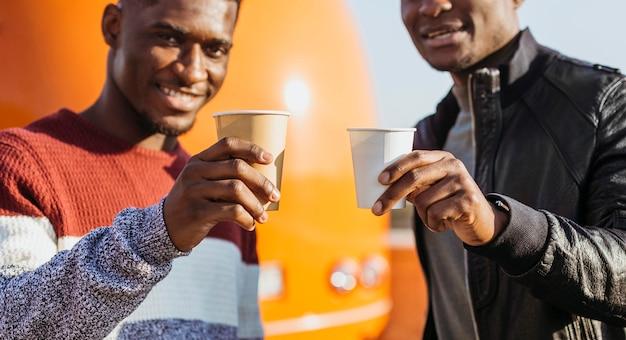 W połowie strzał czarnych mężczyzn pijących kawę przy food trucku