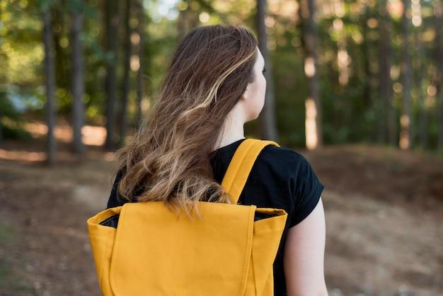 W połowie strzał dziewczyna z plecakiem w lesie
