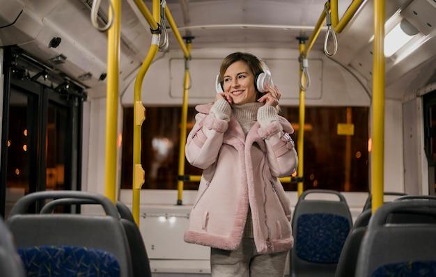 W połowie strzał kobieta jest ubranym hełmofony w autobusie