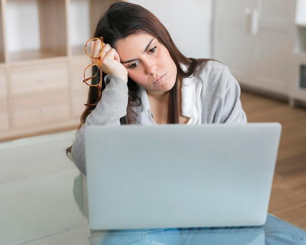 W połowie strzał kobieta pracuje na laptopie i trzyma szkła