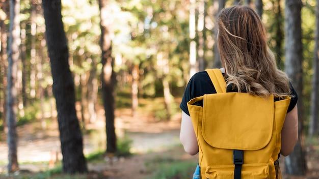 W połowie strzał kobieta z plecakiem w lesie