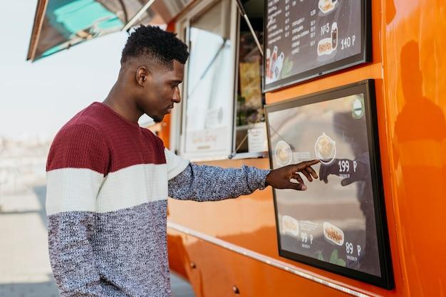 W połowie strzał mężczyzna czytający menu food truck