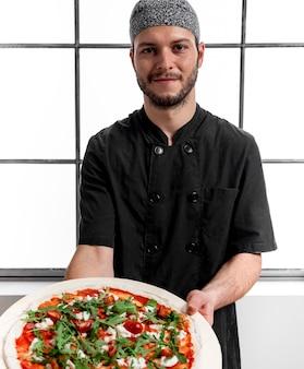 W połowie strzał mężczyzna trzyma deskę do krojenia z pizzą