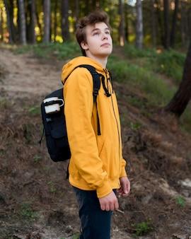 W połowie strzał nastolatka z plecakiem w lesie