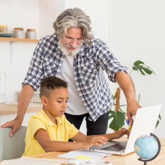 W połowie strzał nauczyciel siedzi obok ucznia przy laptopie