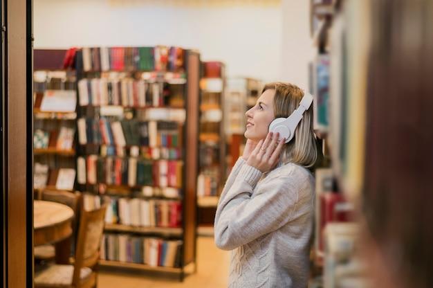 W połowie strzału kobieta trzyma hełmofony na głowie w księgarni