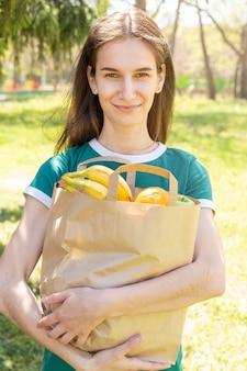 W połowie strzału kobieta trzyma papierową torbę