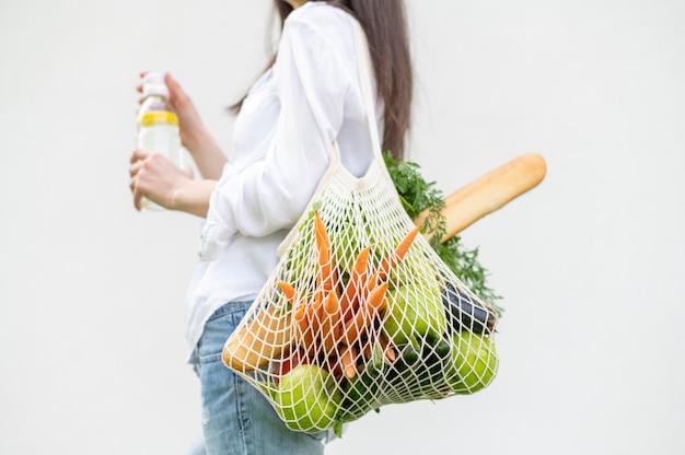 W połowie strzału kobiety mienie wielokrotnego użytku z sklep spożywczy torbą outside