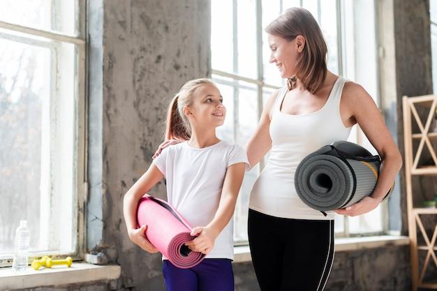 W połowie strzału matka i córka trzyma maty do jogi