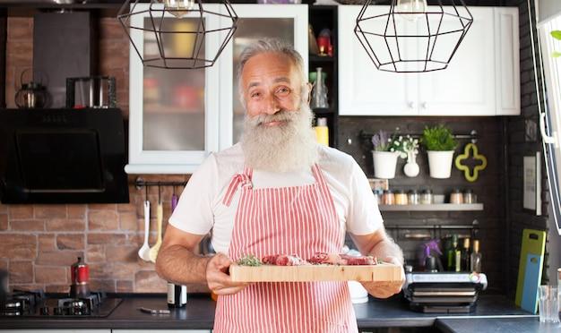 W połowie strzału smiley dojrzały szef kuchni z tnącą deską w ręce. mięso leżące na desce. mężczyzna odizolowany w dobrze zaaranżowanej nowoczesnej kuchni.