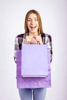 W połowie strzału szczęśliwa kobieta trzyma torby i patrzeje kamerę