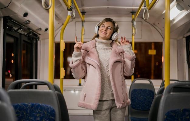 W połowie strzału uśmiechnięta kobieta jest ubranym hełmofony w autobusie