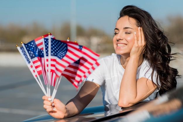 W połowie strzału uśmiechnięta kobieta trzyma usa flaga na samochodzie