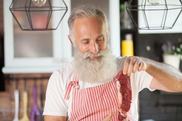 W połowie strzału uśmiechnięty brodaty mężczyzna trzyma surowy kawałek mięsa. trzymać świeżego mięso odizolowywający w kuchni. stojąc w kuchni.