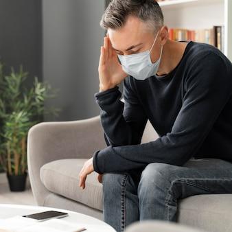 W połowie zdjęcia zmartwiony pacjent z maską w gabinecie terapeutycznym