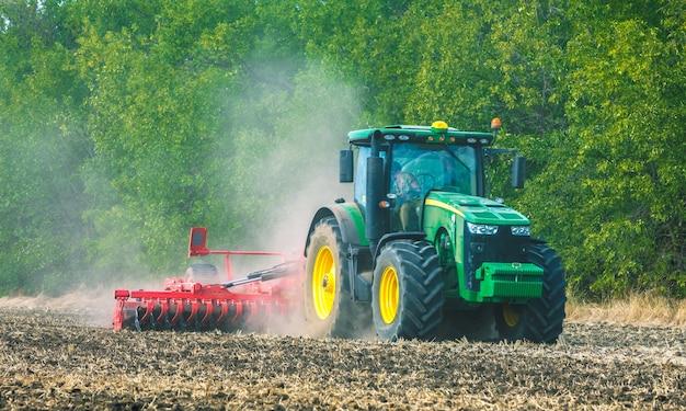 W polu pracuje zielony traktor. uprawa gleby. prace rolnicze.
