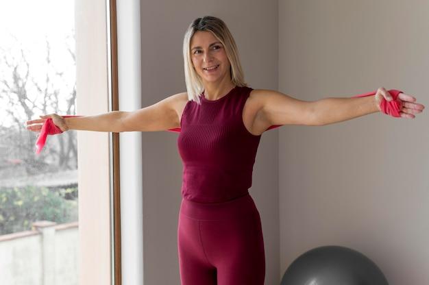 W pomieszczeniu dojrzała kobieta robi ćwiczenia cardio