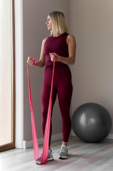W pomieszczeniu dojrzała kobieta robi ćwiczenia fitness