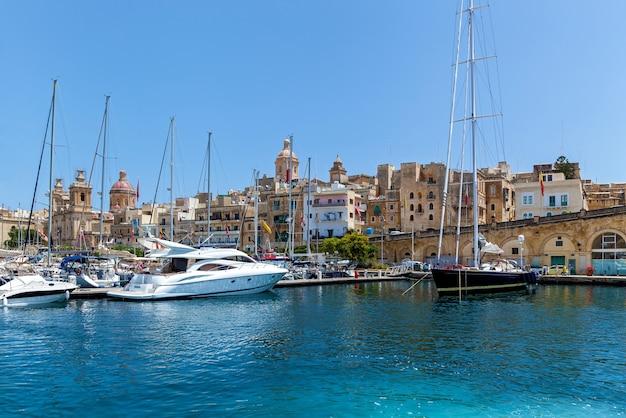 W porcie na tle maltańskim jest dużo zacumowanych jachtów