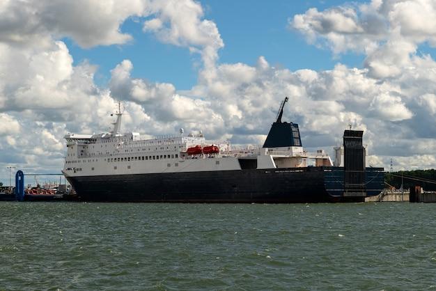 W porcie załadunek dużego frachtowca lub statku wycieczkowego.