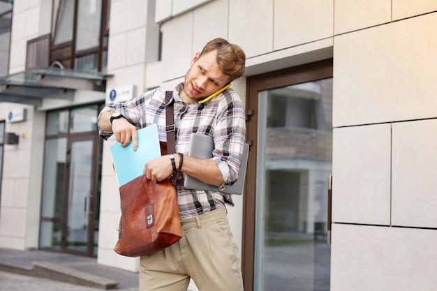 W pośpiechu. ładny, przystojny mężczyzna, wkładając notebook do torby podczas rozmowy przez telefon