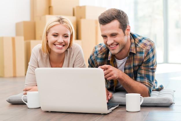 W poszukiwaniu dobrej firmy przeprowadzkowej. wesoła młoda para leży na podłodze w swoim nowym mieszkaniu i patrzy na laptopa, podczas gdy w tle leżą kartony