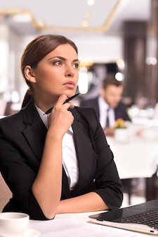 W poszukiwaniu nowych pomysłów na biznes. rozważna młoda kobieta w stroju formalnym trzymająca rękę na brodzie i odwracająca wzrok, siedząc w restauracji
