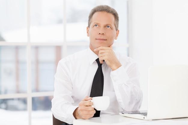 W poszukiwaniu nowych pomysłów. rozważny dojrzały mężczyzna w formalnym stroju siedzi w swoim miejscu pracy i pije kawę