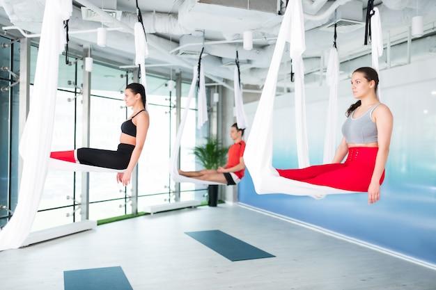 W powietrznym jedwabiu. dwie szczupłe i wysportowane kobiety i mężczyzna siedzący w powietrznym jedwabiu podczas jogi latania