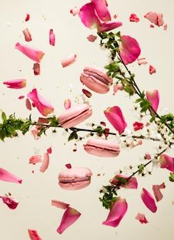 W powietrzu unoszą się różowe makrony i płatki róż z gałązką wiśni na szarej powierzchni